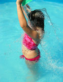 Cooling off. A young girl pours a bucket of cooling water over her head in a swimming pool Stock Image