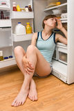 Cooling Off. Young woman in shorts and tank top sitting next to open refrigerator to cool off Royalty Free Stock Images