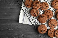Cooling rack with chocolate chip cookies on wooden background, top view. stock images