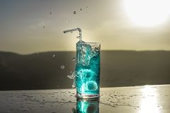 Cooling summer drink concept. Cocktail glasses splashing on sunset. Close up wet glass of cold drink on the terrace. Selective focus stock photography