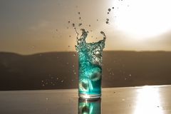 Cooling summer drink concept. Cocktail glasses splashing on sunset. Close up wet glass of cold drink on the terrace. Selective focus royalty free stock images