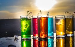 Cooling summer drink concept. Cocktail glasses splashing on sunset. Close up wet glass of cold drink on the terrace royalty free stock photography