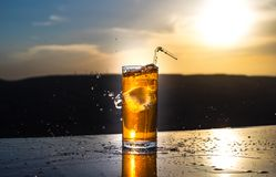 Cooling summer drink concept. Cocktail glasses splashing on sunset. Close up wet glass of cold drink on the terrace stock photography