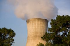 Cooling Tower. Wth Smoke and Pine Trees royalty free stock image
