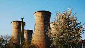 Cooling tower. Inoperable cooling towers near a garden with trees royalty free stock image