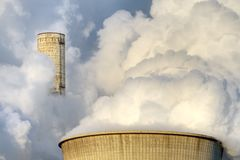 Cooling tower and chimney. Chimneys and cooling towers of a power plant shrouded in steam Stock Photo
