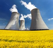 Cooling tower with golden flowering field of rapeseed Royalty Free Stock Photos