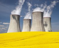 Cooling tower and rapeseed field Royalty Free Stock Photos