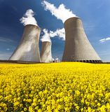 Cooling tower and rapeseed field Stock Image
