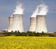 Cooling tower and rapeseed field Stock Images