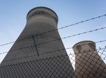 Cooling towers behind barbed wire fence stock photography