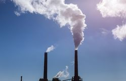Cooling towers and chimneys of a brown coal power plant. Cooling towers and chimneys of coal power plant big blue clouds nuclear atomic danger industry station stock photos