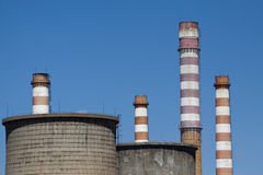 Cooling towers and industrial chimneys against blue sky Stock Photos