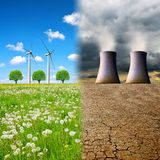 Cooling towers of a nuclear power plant in a devastated landscape and wind turbines on a meadow. Concept of clean and polluting energy generation royalty free stock photo