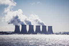 Cooling towers of a Nuclear Power Plant or NPP with thick smoke on blue sky. Background in sunny day. Copy space for text Royalty Free Stock Photo