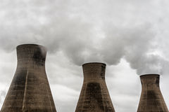 Cooling towers. Row of cooling towers at oil refinery spewing fumes in athmosphere Stock Photos