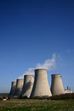 Cooling Towers On A Sunny Day. Cooling towers of a coal-fired power station against blue sky Royalty Free Stock Photo