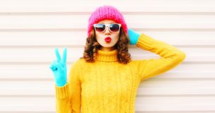 Cooll funny girl blowing red lips wearing colorful knitted yellow sweater pink hat royalty free stock photos
