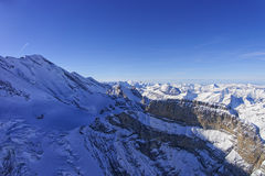 Coomb, wall and peak in Jungfrau region helicopter view in winte Royalty Free Stock Photo