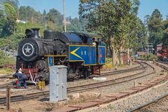 Steam train in rural India. Coonoor, India - March 4, 2018: Railway workers checking a steam engine  used to haul passenger trains on the section of the Blue Stock Images