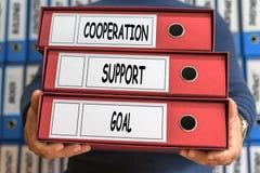 Cooperação, apoio, objetivo, palavras do conceito Conceito do dobrador anel fotografia de stock royalty free