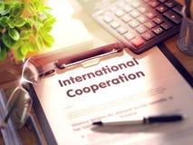 Cooperação internacional - texto na prancheta 3d Foto de Stock Royalty Free