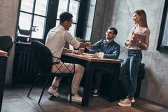 Cooperação na ação Homens modernos novos no sha esperto do vestuário desportivo imagem de stock royalty free