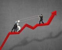 Cooperação para mover o símbolo do dinheiro na seta vermelha Fotografia de Stock Royalty Free