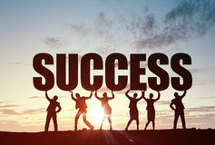 Cooperate for successful work. Business people lifting word success representing collaboration concept royalty free stock photo