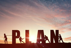 Cooperate for successful work. Business people pulling word plan representing collaboration concept stock photo