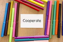 Cooperate text concept. Felt-tip pen and note on a wooden background and cooperate text concept royalty free stock photos