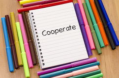 Cooperate text concept. Felt-tip pen and notepad on a wooden background and cooperate text concept stock photography