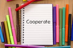Cooperate text concept. Felt-tip pen and notepad on a wooden background and cooperate text concept royalty free stock image