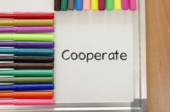 Cooperate text concept. Felt-tip pen and whiteboard on a wooden background and cooperate text concept stock image