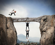 Cooperate to achieve a goal. Businessmen cooperate to keep a log and pass a colleague royalty free stock photos