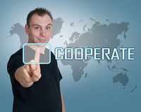 Cooperate. Young man press digital Cooperate button on interface in front of him stock photography
