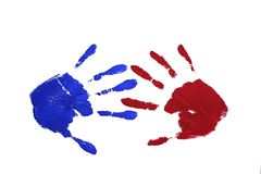 Cooperation. Marks of two hands (paint: red and blue) opposite each other with matching fingers - symbol of cooperation, collaboration and match Royalty Free Stock Photos