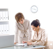 Cooperation. Senior businesswoman teaching younger assiciate in office, smiling Stock Photos