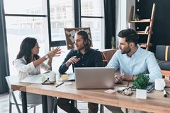Cooperation in action. Group of young modern people in smart casual wear working together while sitting in the office royalty free stock image