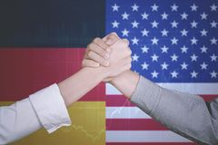 Cooperation with German and American flag. Closeup of two business people is shaking hands for a cooperation agreement with German and American flag in the Royalty Free Stock Photo
