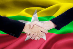 Cooperation handshake with flag of Myanmar Royalty Free Stock Photo