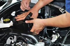 Cooperation in vehicle repairing work. Technicians cooperate in repairing engine of vehicle, shown as teamwork, cooperation concept in working, or service for Royalty Free Stock Photo
