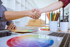 Cooperation of Young creative graphic designer working on workspace and shaking hands after successful of new project, putting. Hands together royalty free stock photography
