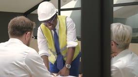 Coordenador africano no capacete e grupo de arquitetos que discutem o projeto na sala de reunião filme