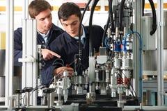 Coordenador And Apprentice Working no equipamento na fábrica fotos de stock