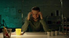 Coordenador arquitetónico capaz dos jovens que trabalha horas atrasadas em seu escritório O escritório é escuro somente sua luz d video estoque