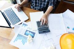 Coordenador asiático, mulher do arquiteto que usa a calculadora para explicar imagens de stock royalty free