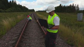 Coordenador cansado na estrada de ferro com portátil filme