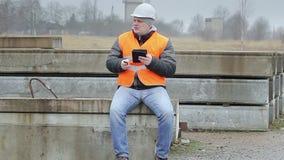 Coordenador com o PC do telefone celular e da tabuleta nos painéis concretos vídeos de arquivo