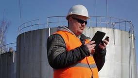 Coordenador com o PC do telefone celular e da tabuleta perto do tanque de óleo filme